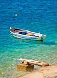 Old wooden fishermen boat on turquoise beach Royalty Free Stock Images