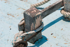 Old wooden fishing boat cleat with rope wrapped around. Stock Photo