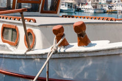 Old wooden fishing boat cleats with rope wrapped around. Royalty Free Stock Photography
