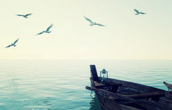 Old wooden fishing boat floating over calm blue sea and sky. 3D rendering Stock Images