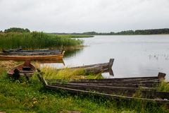 Old wooden fishing boat. Near the summer lake shore Stock Images