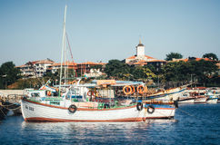 Old wooden fishing boat in port against the backdrop of the Church Of The Holy Virgin in ancient Nessebar. Royalty Free Stock Image