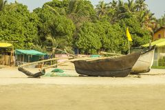 Old wooden fishing boat on the sand against the backdrop of green jungles and houses. A old wooden fishing boat on the sand against the backdrop of green jungles stock photos