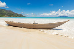 Old wooden fishing boat on sand with blue sky and water backgrou Stock Images