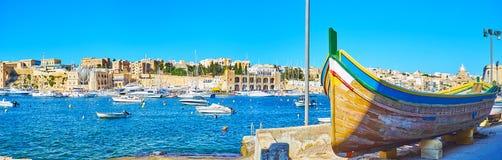 Panorama of Kalkara marina with old wooden boat, Malta. The old wooden fishing boat on shore at Kalkara marina, seen from Birgu seaside promenade, Malta stock photography