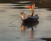 Old wooden fishing-boat at sunset. Royalty Free Stock Photography