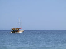 Old wooden fishing boat trawler over calm blue sea Stock Photography