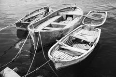 Old wooden fishing boats, black and white. Old wooden fishing boats moored in small port of Avcilar, district of Istanbul, Turkey. Black and white retro stylized Stock Photos