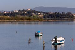 Fishing boats in the morning light. Old, wooden, fishing boats on the lake Halkiopoulou on a spring day Corfu Island, Greece Stock Photo