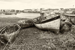 Old Wooden Fishing Boats. These old fishing boats lie tied to the shore, probably never to do a days work again Royalty Free Stock Photography