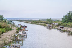 Old wooden fishing houses in the river Stock Photography