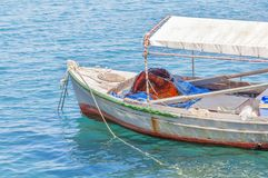 Old wooden fishing red boat tied on dock. Close Stock Image