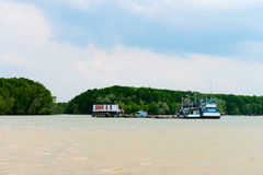 Old wooden fishing village with two ships on river Royalty Free Stock Photo