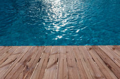Old wooden floor and blue water in swimming pool Royalty Free Stock Photo