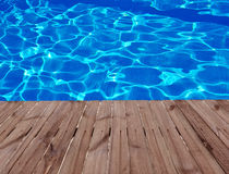 Old wooden floor and blue water in swimming pool Royalty Free Stock Photography