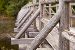 An old wooden foot bridge running over a swampy lake Royalty Free Stock Image