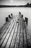 Old wooden foot bridge in sea. Old long and worn wooden foot bridge in water Royalty Free Stock Image