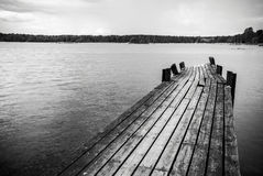 Old wooden foot bridge in sea. Old long and worn wooden foot bridge in water Stock Images