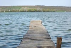 Old wooden footbridge over the lake. Royalty Free Stock Photos