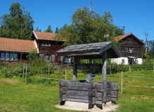Old wooden fountain in Fryksas. Old wooden fountain and historic buildings in Fryksas (Dalarna in Sweden). This little village has more than 200 shielings (so Stock Photos
