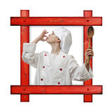 Old wooden frame against a white background with a young boy dressed as chef with wooden spoon on white background. Royalty Free Stock Photos