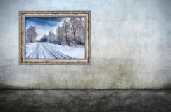 Old wooden frame with beautiful winter landscape on dirty wall Stock Photos