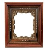 Old wooden frame with embellishment. Antique wooden frame with fancy old daguerreotype gold metal insert Royalty Free Stock Photography