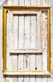 Old wooden frames with gilding hang on an old wooden wall with peeling paint.  stock image