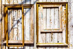 Old wooden frames with gilding hang on an old wooden wall with peeling paint.  stock images