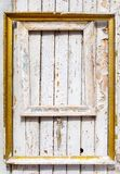 Old wooden frames with gilding hang on an old wooden wall with peeling paint royalty free stock photo