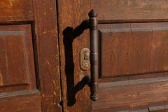Old wooden front door with iron handle. Horizontal shot. Shut. Shadow from the door handle. Background. Texture royalty free stock image