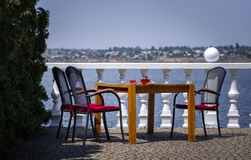An old wooden furniture on a restaurant`s balcony on a blue sky background. Relaxing place for vacation. Copy space. Stock Photo