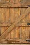 Old Wooden Gate with Black Hinges. An old, weathered, worn, wooden gate with heavy grains, nail marks and black iron hinges Stock Image