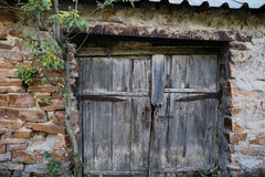 Old wooden gate doors and stone wall Stock Image