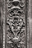 Old wooden gate engraved with demonic figures. Stock Photos
