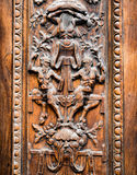 Old wooden gate engraved with demonic figures. Detail of old wooden gate engraved with demonic figures Stock Image