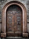 Old wooden gate engraved with demonic figures. Old wooden gate with stone vault engraved with demonic figures Stock Photos