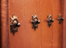 Old wooden gate fixed with large brass rivets in Catalonia, Spai Stock Photo