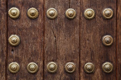 Old wooden gate fixed with large brass rivets in Cordoba, Spain Royalty Free Stock Images