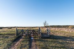 Old gate into a great plain landscape. Old wooden gate into the Great Alvar, an unesco world heritage site at the swedish island Oland royalty free stock photos