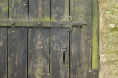 Old wooden gate with hand prints. Old wooden gate with green hand prints in stone wall near Hartington, England Stock Images