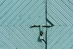 Old wooden gate with metal padlock. Stock Images