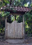 An Old Wooden Gate with a Tiled Roof stock photo