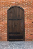 Old wooden gates and walls of red brick. Royalty Free Stock Images