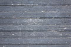 Old wooden gray fence made of planks with peeling paint, cracks and white spots close up. horizontal lines. rough surface texture royalty free stock photos