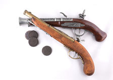 Old wooden guns and coins. On white background Royalty Free Stock Image