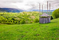 Old wooden hay shed on grassy hillside. Beautiful scenery of mountainous rural area in springtime Stock Images