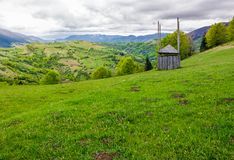 Old wooden hay shed on grassy hillside. Beautiful scenery of mountainous rural area in springtime Royalty Free Stock Photography