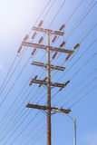 Old wooden high voltage post against sun and blue sky. Stock Photography