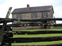 Old Civil war era wooden home. An old wooden home with log fence royalty free stock photo